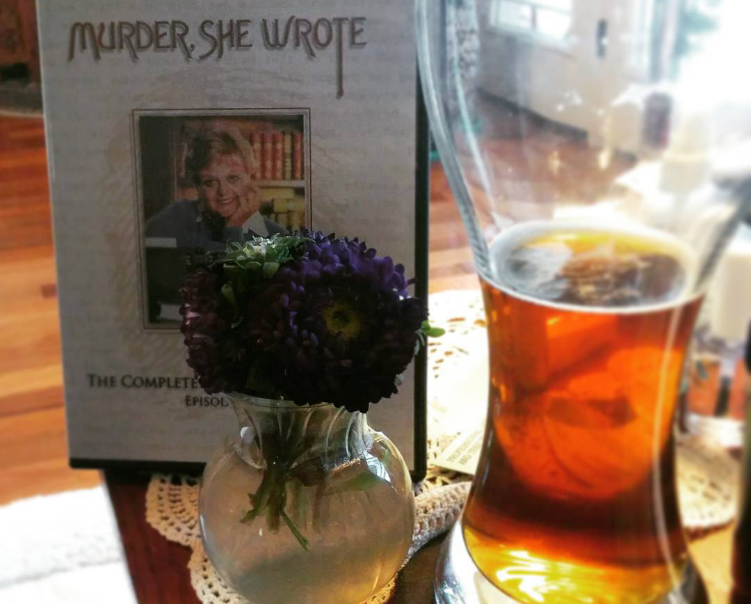 Photo of a glass of beer next to the Murder She Wrote dvds and a vase of purple flowers.